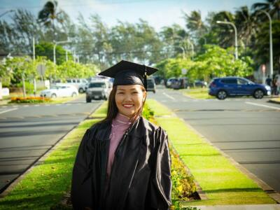 Ngeskebei smiling wearing a black cap and gown with a grass field and two roads behind her.