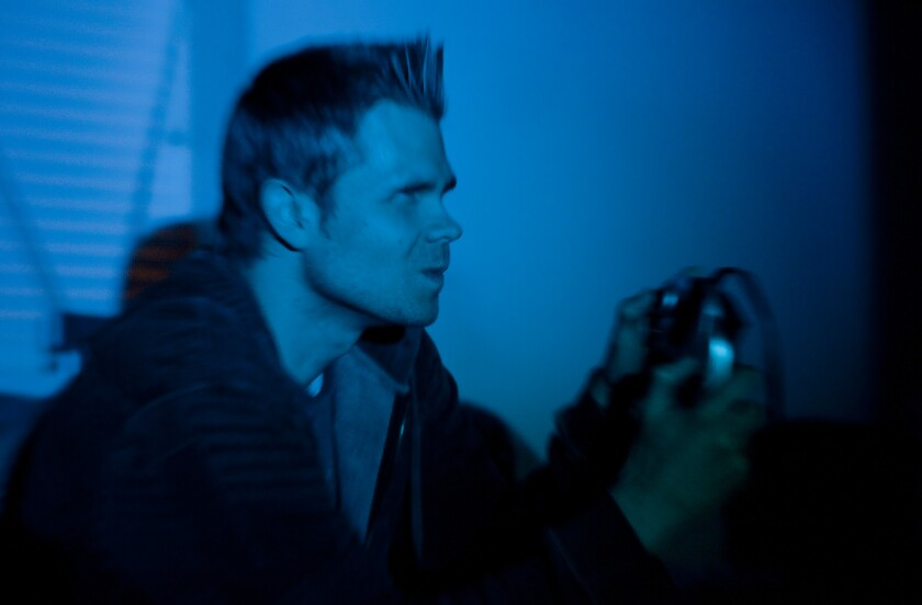 Man Playing Video Games in Dark Room