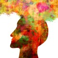 Silhouette of a person's head in multiple colors connecting with a cloud of thought.