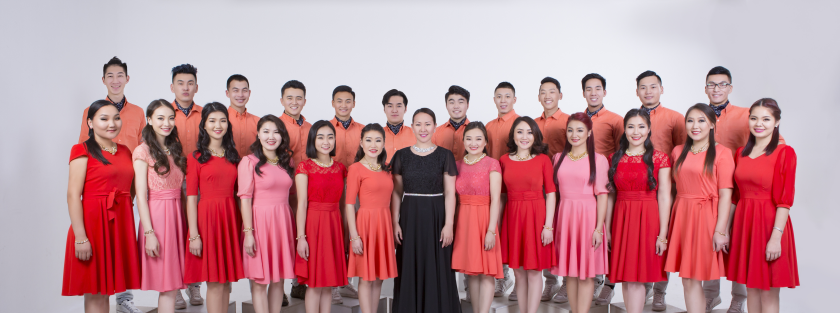 A row of over 10 women stand in front wearing red and pink dresses with a women in the middle wearing a black dress and 12 men in. the back wearing peach colored shirts.