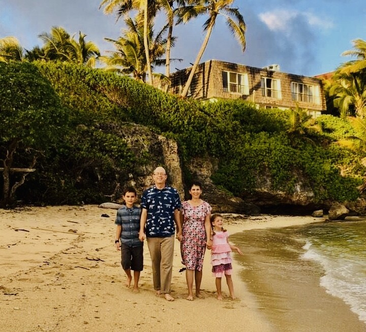 Matthew and Suzanne Bowen on the beach holding hands with their two children with trees, plants, and building in background.