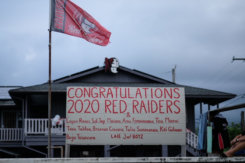 A sign in Laie with the names of Kahuku High School graduates and a Red Raiders flag at a house.