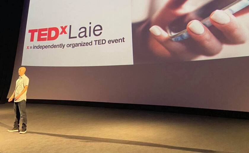 A speaker at TEDxLaie stands on the stage with the event logo in the background