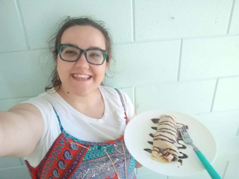 Laura Hinze smiles wearing a white shirt and colorful orange and blue dress holding up a plate with a crepe with chocolate syrup with a white wall behind her.