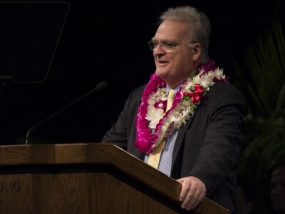 Dan Stout wearing colorful flower leis speaking behind a brown podium in a dimly lit auditorium.