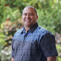 A Polynesian man wearing a blue patterned button up shirt smiling at the camera. Green plants are visible in the background.