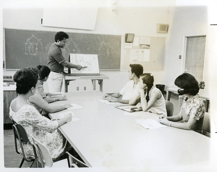 Old black and white photo of Ropeti Lesa teaching, pointing towards a whiteboard with six students at the table looking at him.