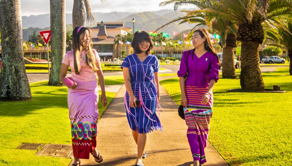Three Myanmar students walk on the sidewalk at the entrance to BYU–Hawaii.