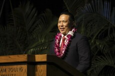 Chun speaking at a wooden pulpit wearing a black suit and red tie with a pink flower lei and palm leaves behind him.