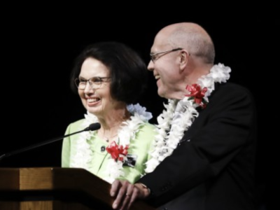 Elder and Sister Osguthorpe stand together at the podium wearing leis