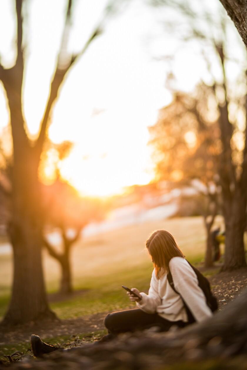 Teenage girl scrolls through social media on a mobile phone.