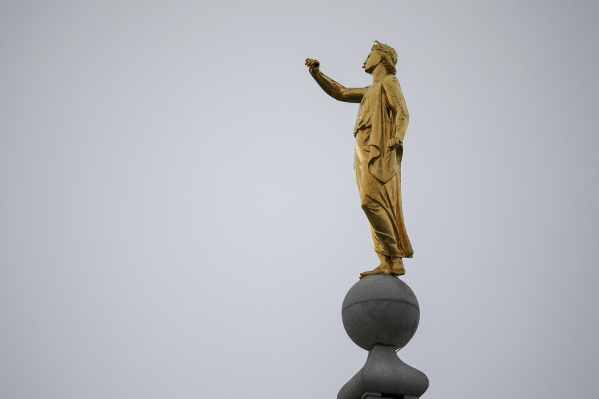 The Angel Moroni statue atop the Salt Lake Temple stands without his trumpet.