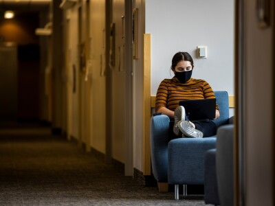 Girl sitting in a chair with a mask on the computer