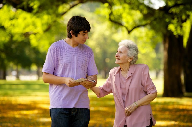 Young man and elderly woman visitinhg