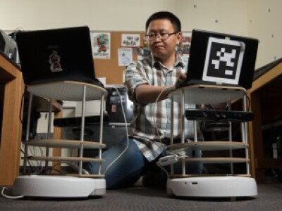 Daqing Yi works to program robots in a computer science laboratory