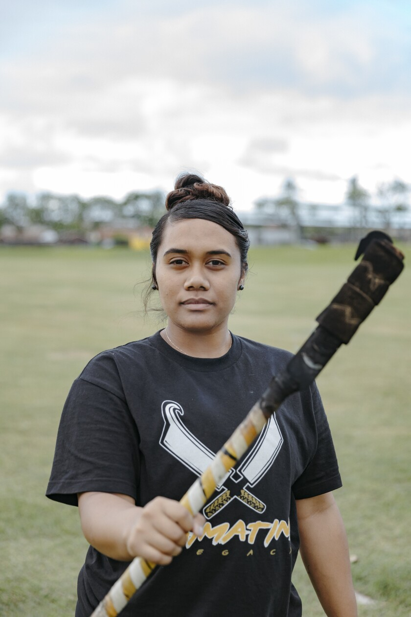 Jeralee Galeai wearing a black T-shirt with fireknives on it. She is holding a fireknife while standing on the grass at BYUH campus.