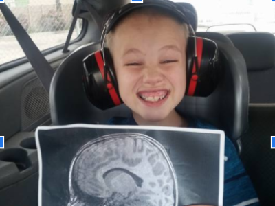 Young boy holding a picture of a brain scan.