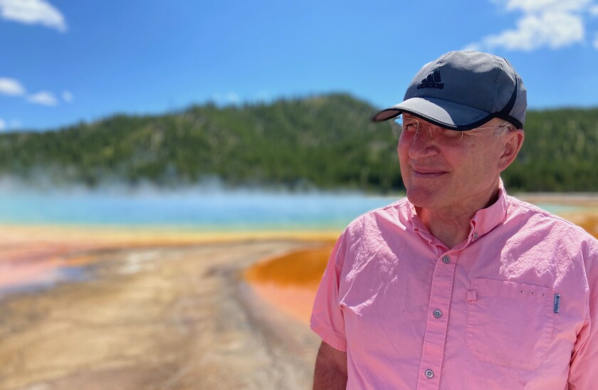 Gale Pooley wearing a pink button up shirt and grey adidas hat stands outside with orange ground water, blue mist, and green hills behind him.