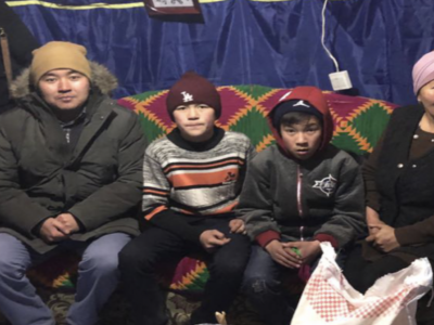 A Mongolian family sits on a couch in a house wearing winter clothing