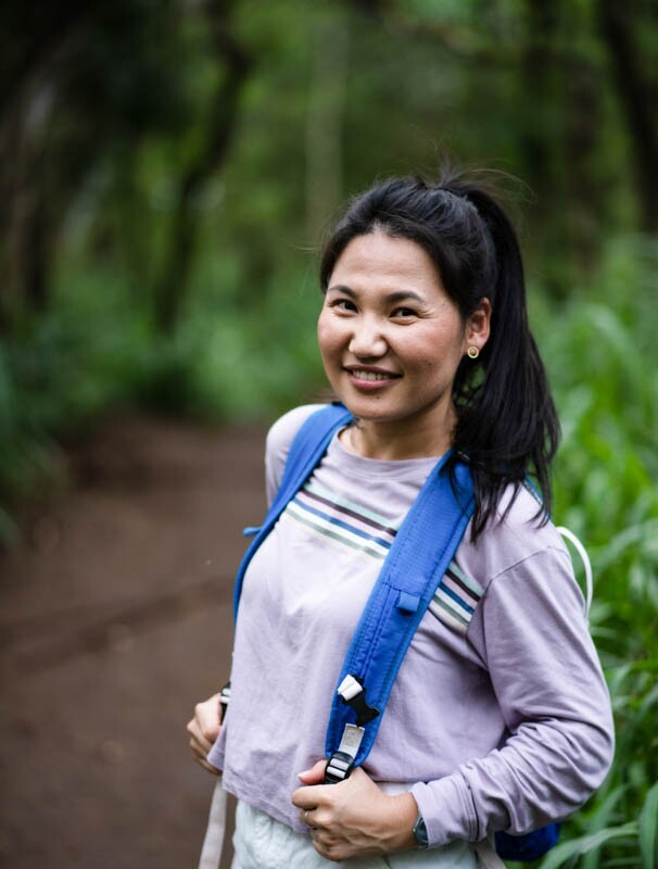 Dalaichuluun smiling wearing a long-sleeved purple shirt and a blue backpack with greenery behind her.
