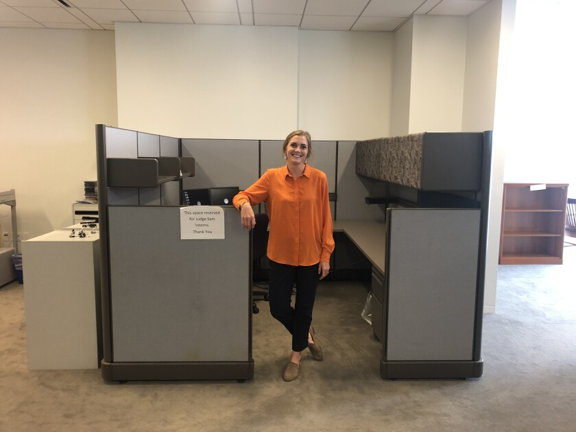 Melissa Jo Townsend standing in front of the cubicle reserved for Judge Sam's interns.