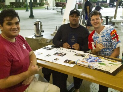Three students attending the missionary event sit at a table with mission memorabilia on it.