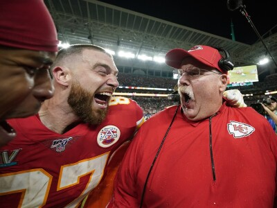 Kansas City Chiefs' head coach Andy Reid celebrates while standing next to a couple of his players