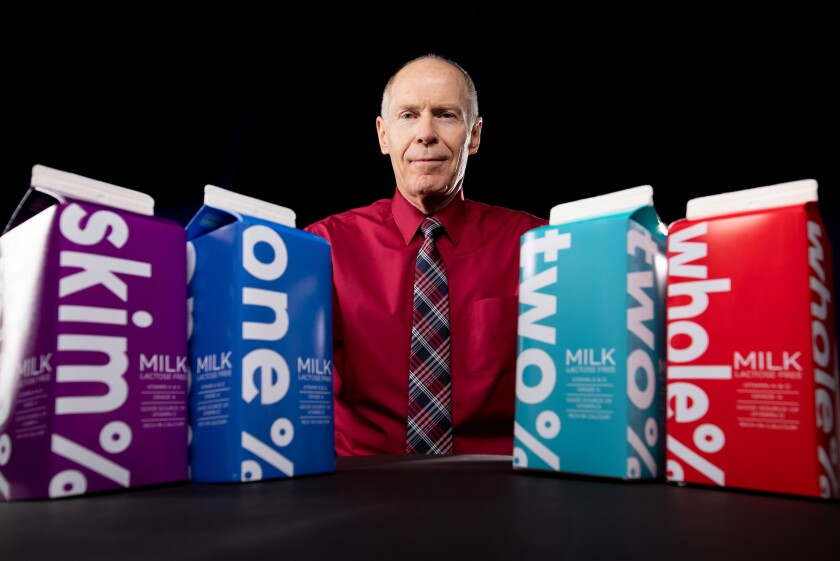 Exercise science professor Larry Tucker poses with different milk cartons
