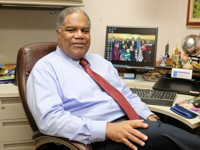 Marcus Martins sits in a chair in his office with a picture of his family on the computer desktop in the background
