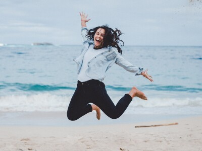 Davia Kaopua jumps in the air on a beach.