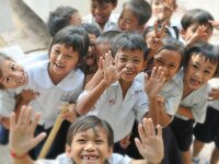 Image of elementary age school children smiling and waving