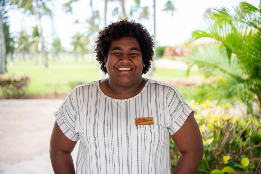 Tavuto tersenyum mengenakan kemeja bergaris putih dan hitam dengan label kayu dengan tanaman hijau di belakangnya.