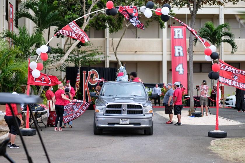 A truck carrying a graduating senior drives through a celebration area at Kahuku High School.