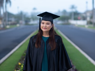 Battulga stands wearing a blue dress and black graduation cap and gown with two roads and grass behind her.