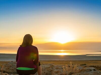 A woman sits on the shore and stares off into the distance at a sunset