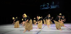 Women bending down doing arm movements while dancing wearing black shirts, black and yellow Polynesian-styled skirts, a white necklace and yellow feathers in their hair with a black background and screen behind them.