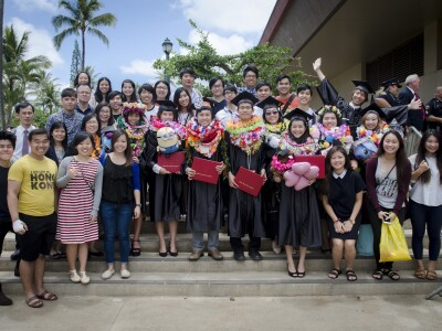 A group photo of students smiling at the camera. Graduating students standing in the middle, wearing their graduation gowns while holding their red diploma, surrounded by a bunch of students.