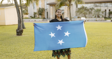 A woman stands wearing a black shirt and a black skirt with a pineapple design on it holding the Micronesian flag that's blue with four white stars in the middle with a field behind her.