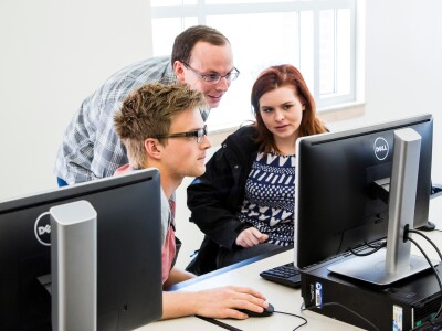 Three people looking a computer screen
