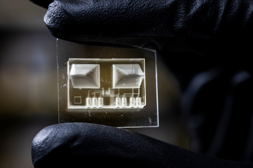 Close up image of a microfluidic device being held by someone with black gloves