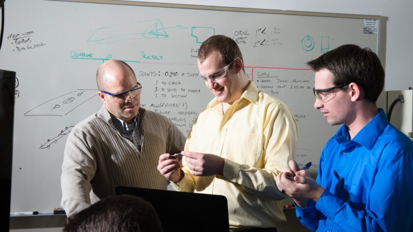 A professor mentoring several students in a lab environment