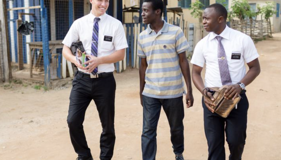 Missionaries in Ghana walk with a local man down the street