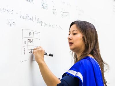 Tahira Carrol, a Hindi instructor, writes on a whiteboard as she teaches a class.