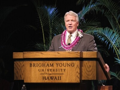 Stephen Owen stands at a podium that says Brigham Young University Hawaii.