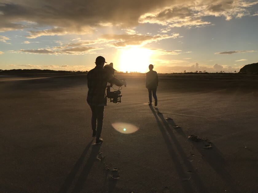 A film crew member films a youth actor walking into a sunset on a beach