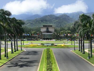 An aerial view of the palm tree-lined Kulanui street that leads into the entrance of BYU-Hawaii. At the center of the frame is the flag circle and the David O McKay building against a backdrop of the Ko'olau mountains.