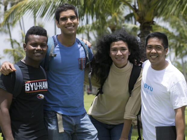 Group of four multicultural students (three male, one female) smiling together