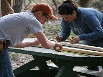 Two Construction Management students working on a project in the field