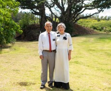 Elder Tam, wearing grey suit pants a white button up shirt and a red and blue striped tie, next to Sister Tam, wearing a white and black long dress, with a field and trees behind them.