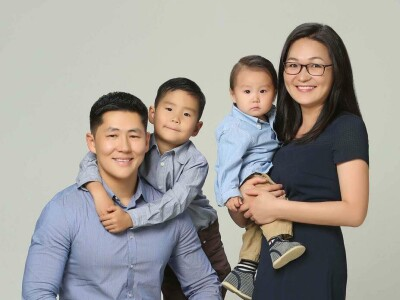 Gankhuyag Tsogoo (left) sits with his sons arms around his neck and his wife on his right side holding his younger son, the boys wearing blue button up shirts and his wife wearing a dark blue dress with a grey/white wall behind them.
